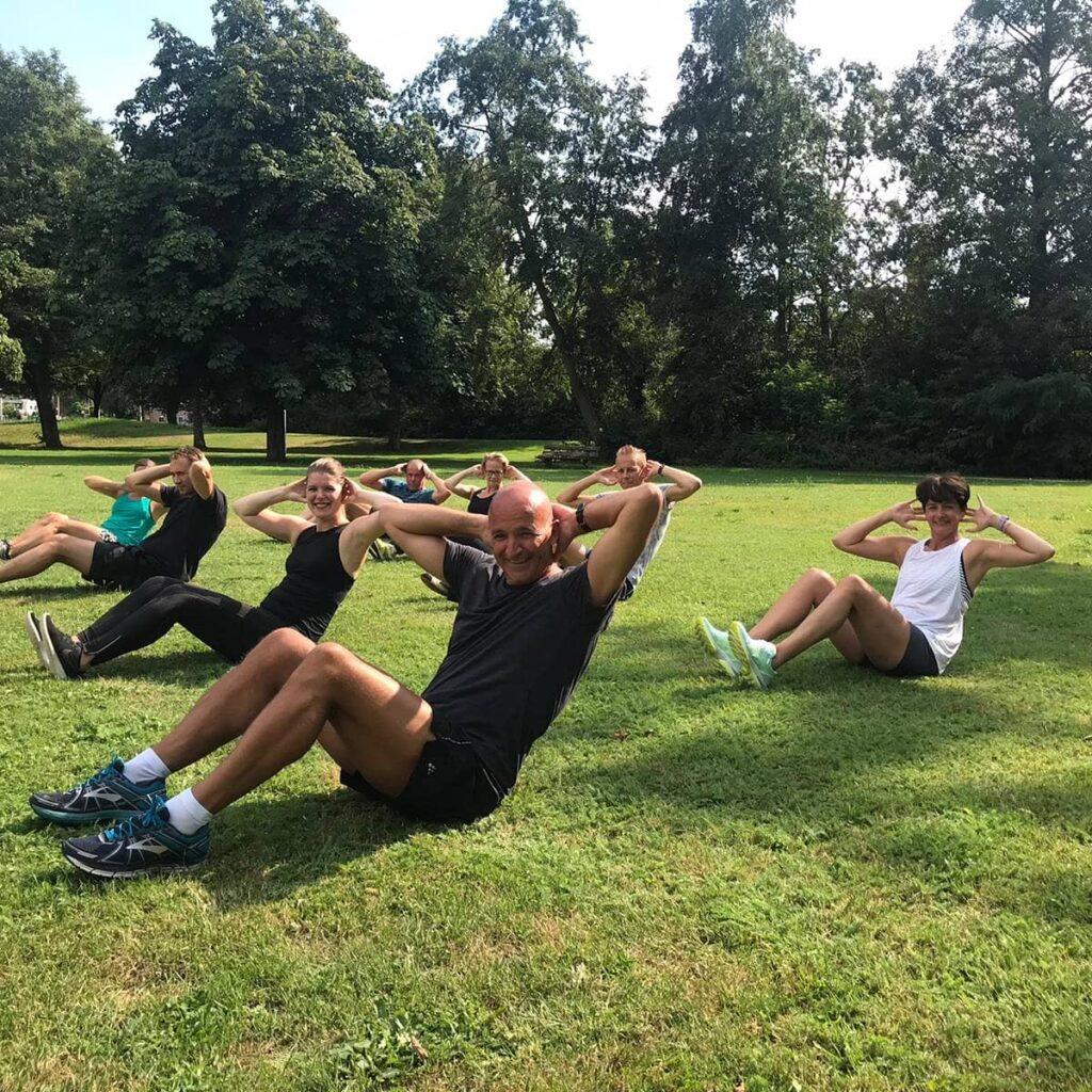 Sporters doen buikspiertraining tijdens Bootcamp & Yoga in het park