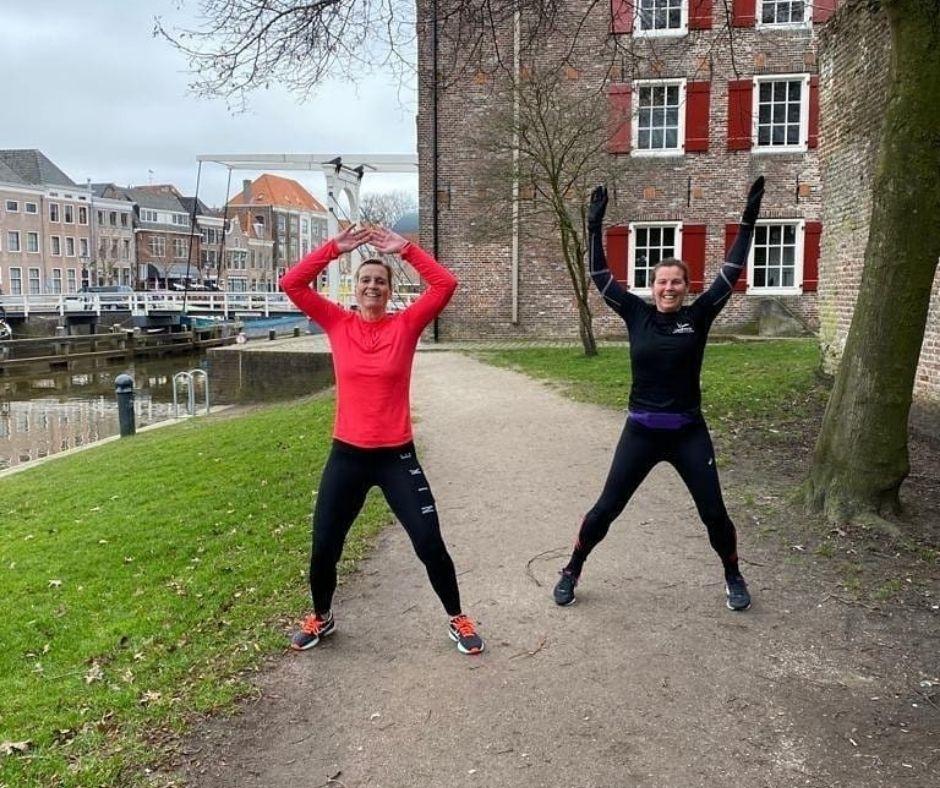 Twee vrouwen doen jumping jacks tijdens sportroute door Zwolle
